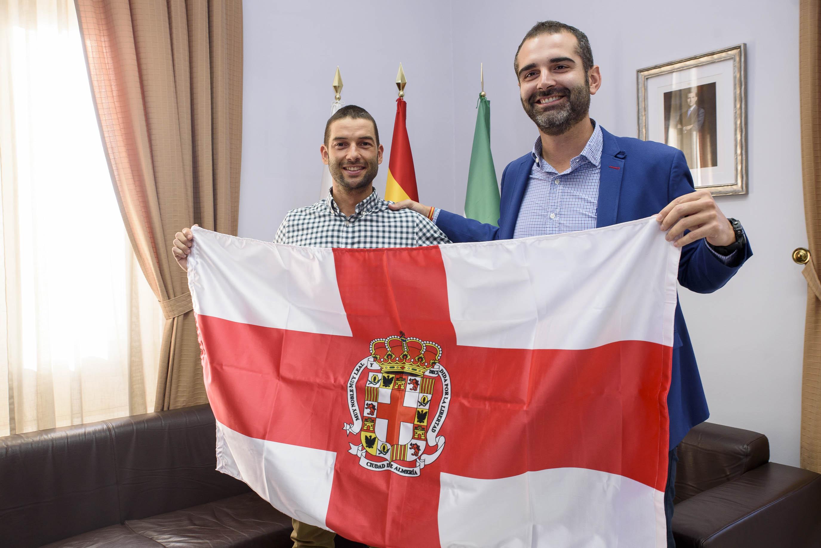 El alcalde hace entrega de una bandera de Almería al triatleta Rafael Lao, que participa en el Campeonato del Mundo Ironman de Hawaii